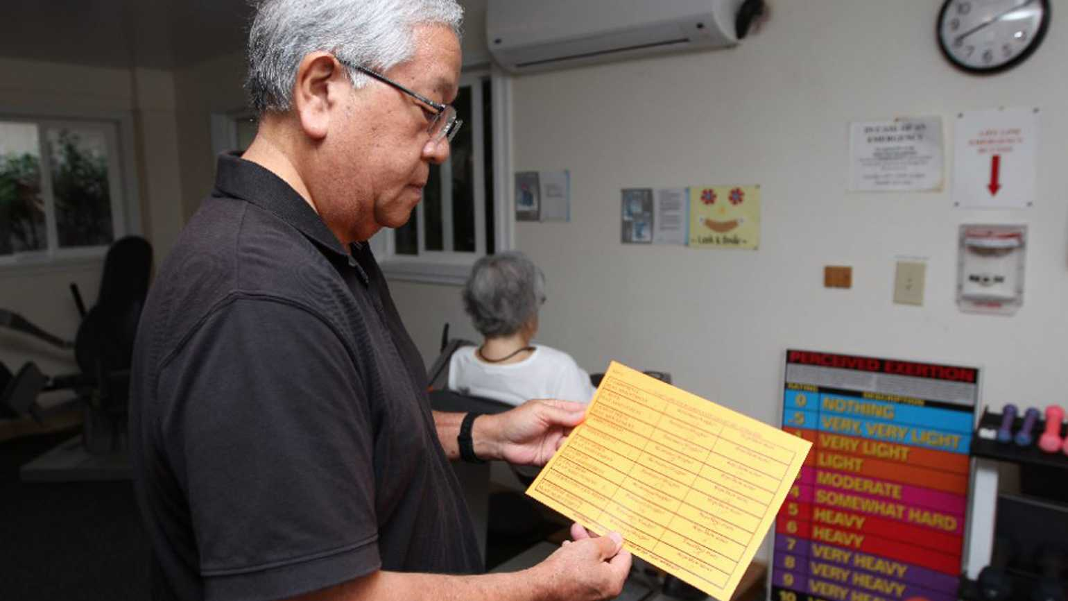Randy Kimura shows the sheet that he and his mother-in-law, Janet Nakashima, use to keep track of her workouts.