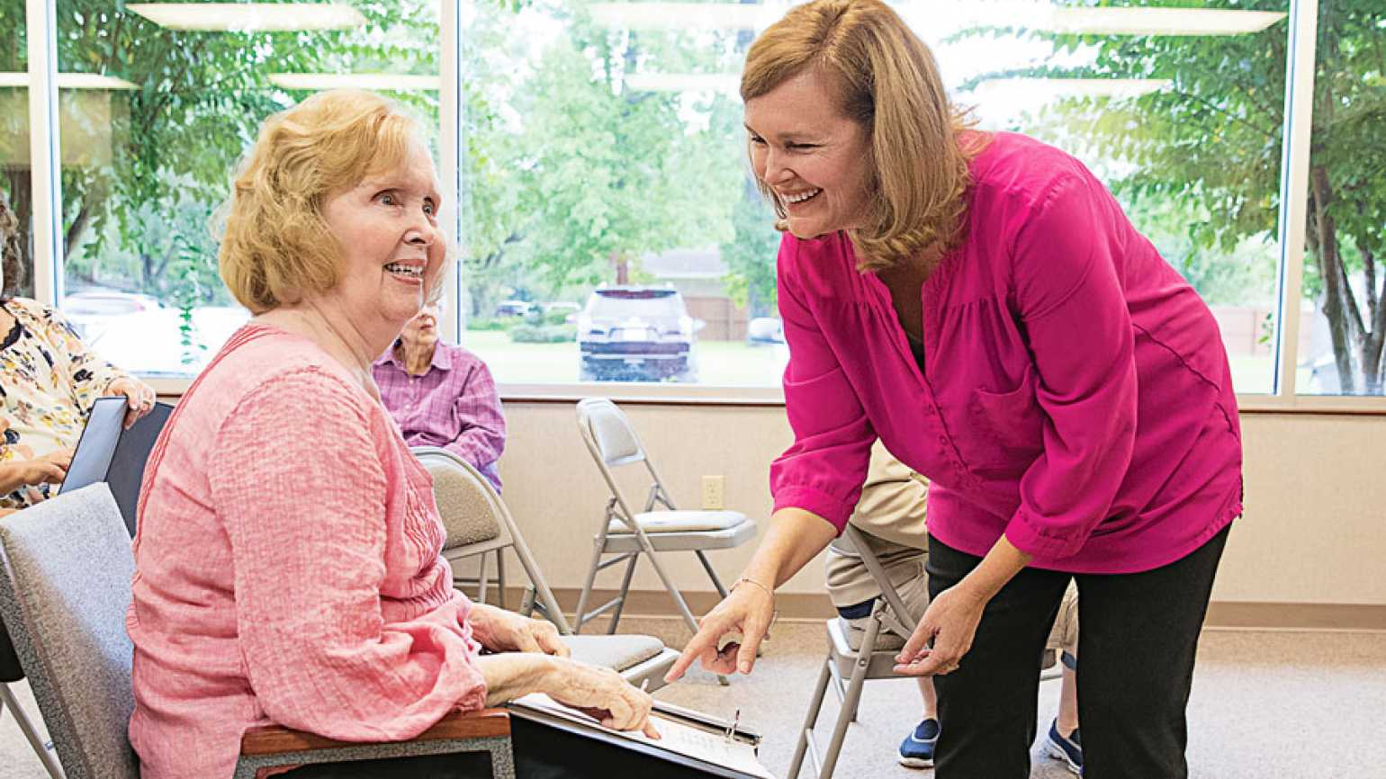A smiling young woman assists her mother, who is dealing with Alzheimer's