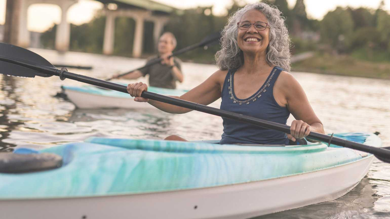 An ethnic senior woman smiles while kayaking with her husband.