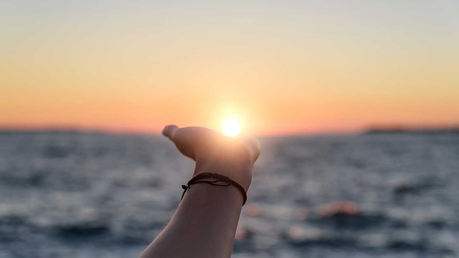 A woman's hand reaches out toward the sun rising over the ocean