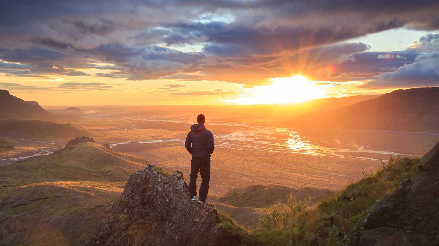 A hiker takes in a mountain sunrise