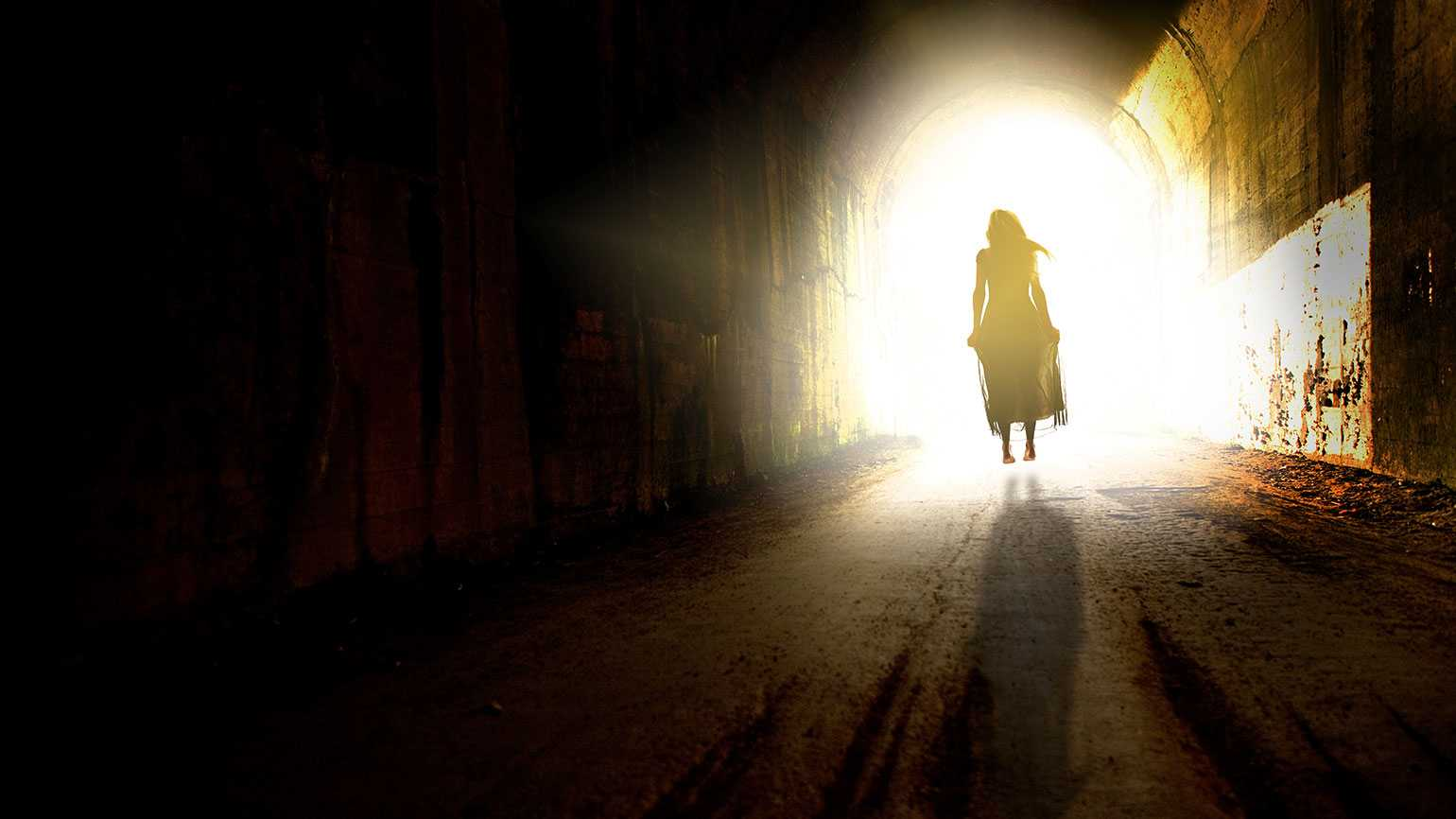 A woman walks down a dark corridor toward a heavenly light