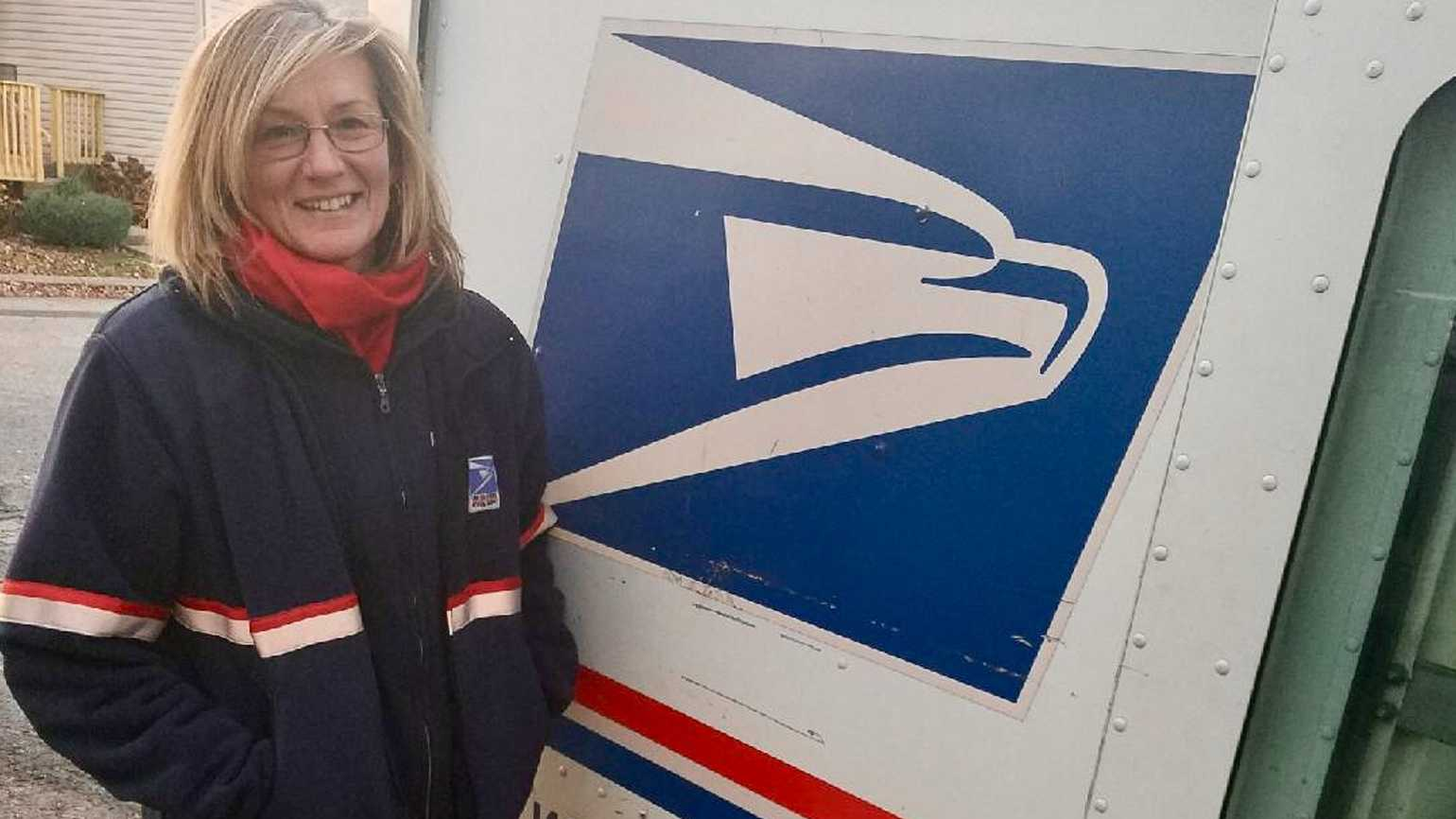 Mail carrier Lisa Sweeney by her mail truck