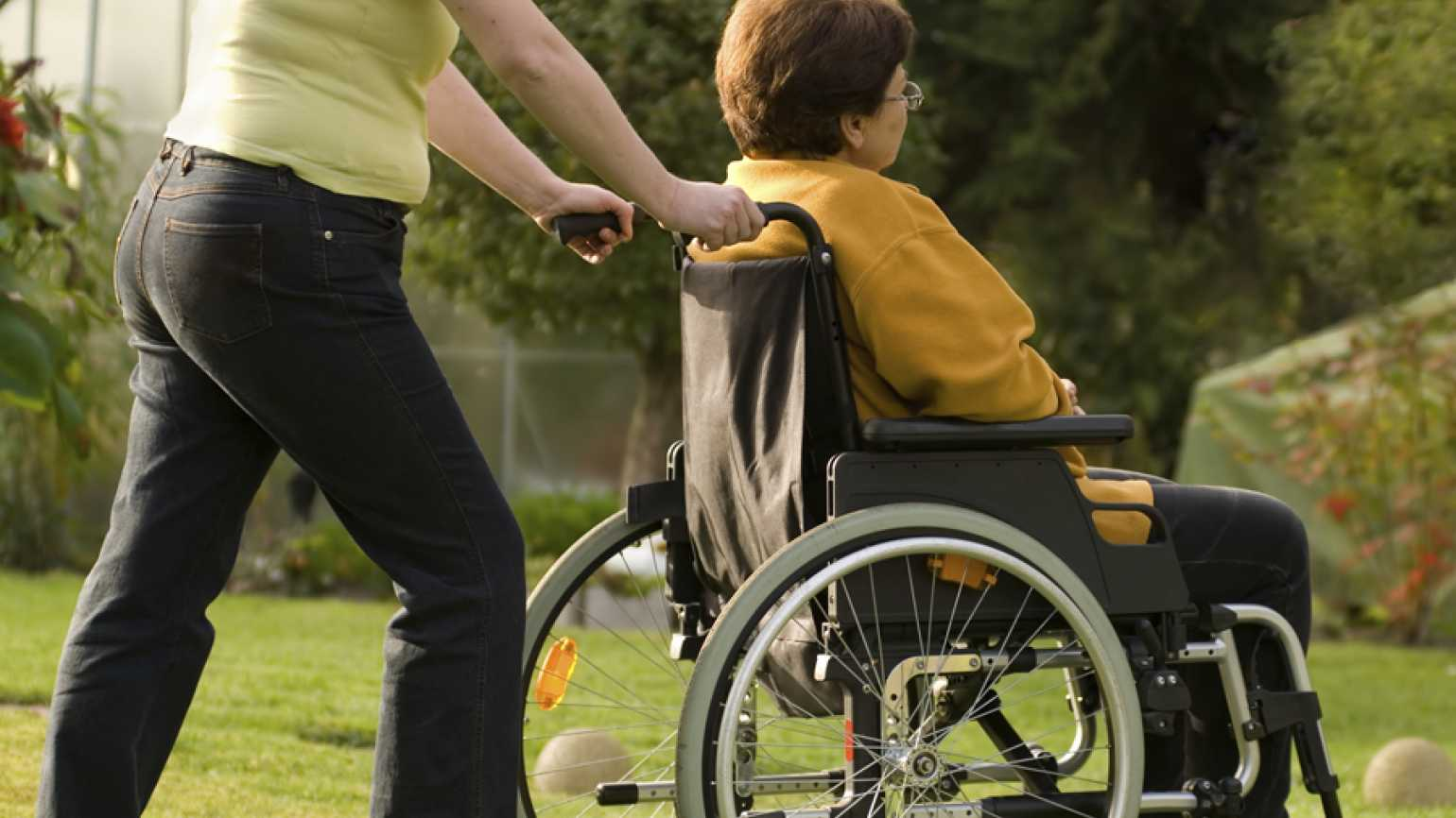 caregiver pushes loved one in a wheelchair losing own identity