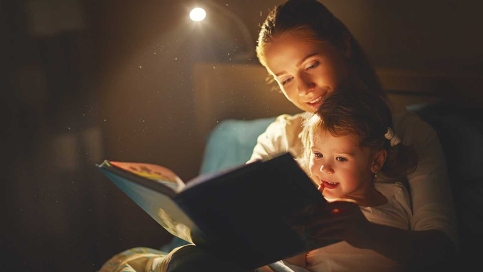 A young mother reading a bedtime story to her daughter.