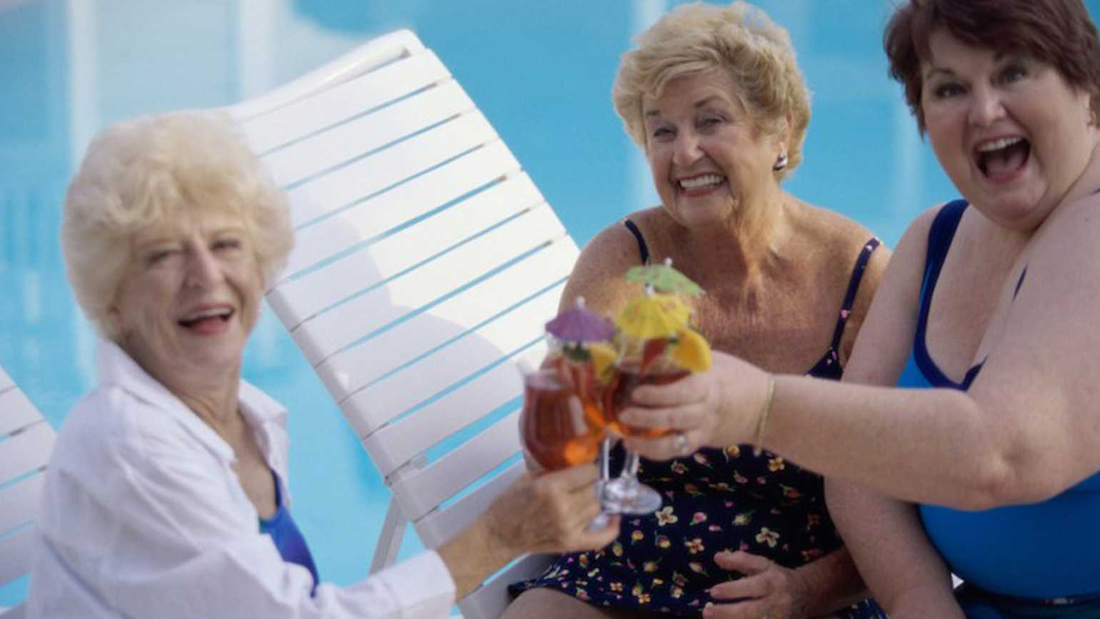 A group of senior citizen women enjoying themselves by the pool side.