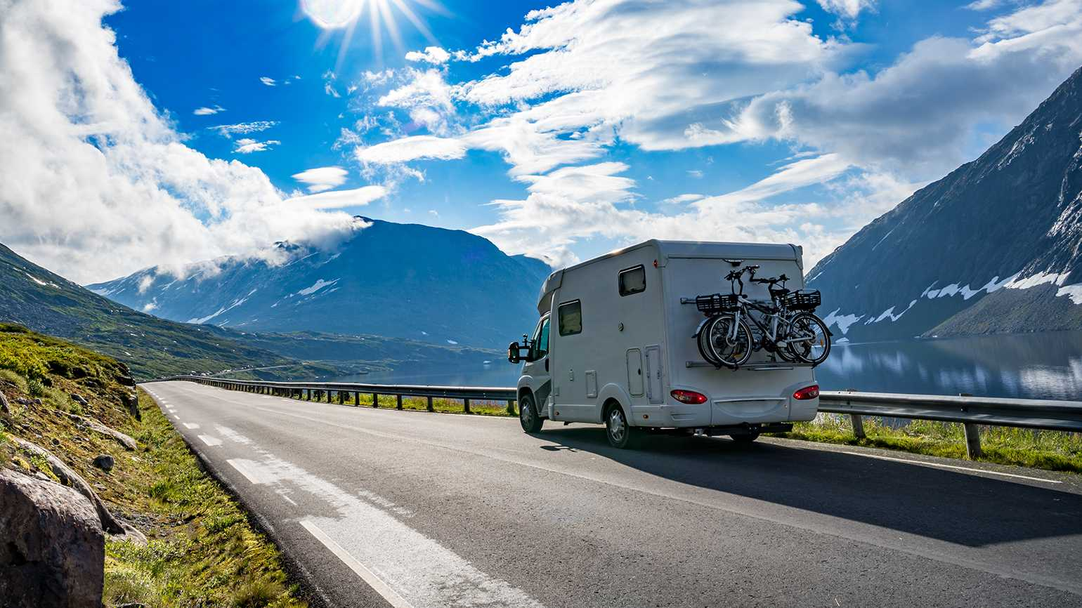 An RV on the open road in the mountains