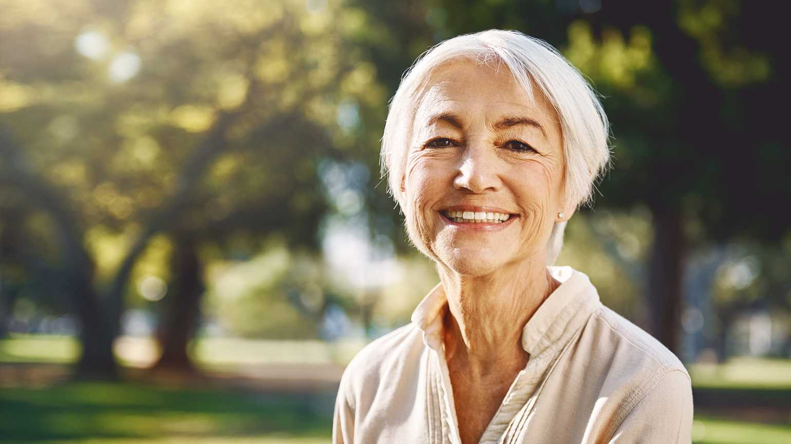 A woman smiling as she spends time outdoors in the sunlight.