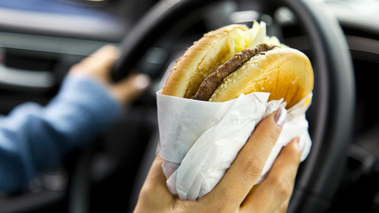 how to avoid stress eating; man holds a hamburger in one hand and the black steering wheel of a car in the other