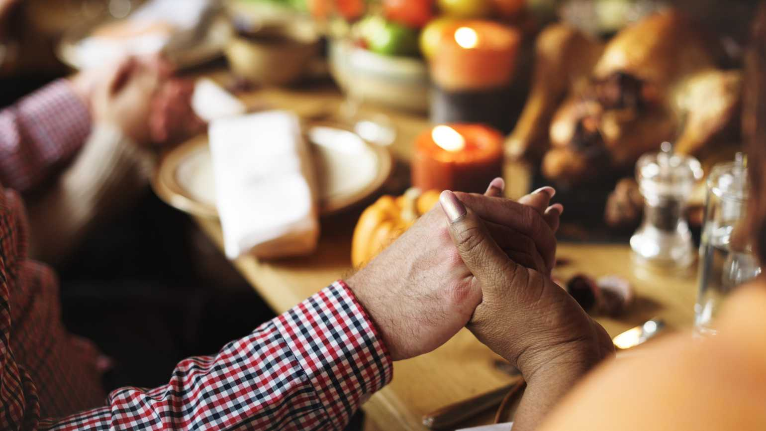 Thanksgiving guests holding hands around the table in prayer.