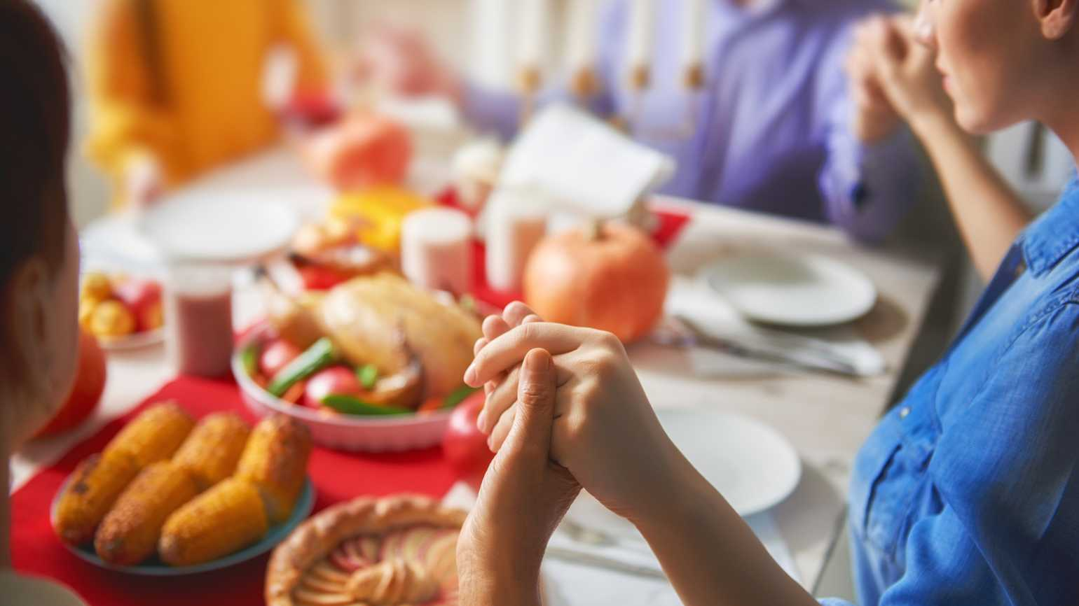 A family on Thanksgiving holding hands in prayer around the dinner table.