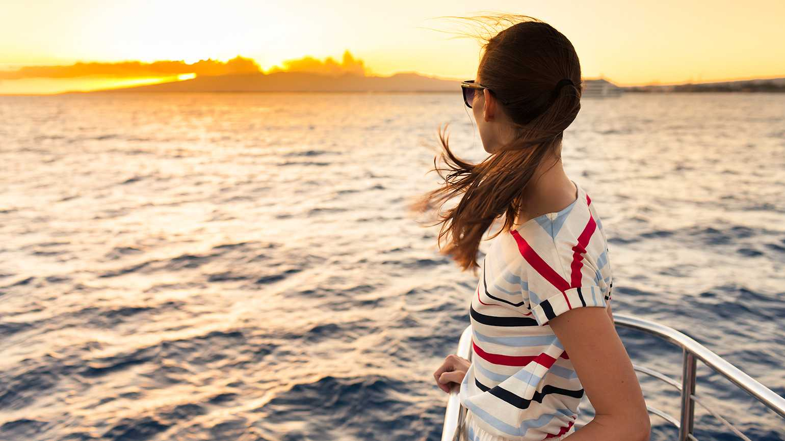 A woman rides a ferry at sunset