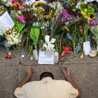 Raymond Smith of Charleston kneels in prayer the front of the Emanuel AME Church before a worship service, Sunday, June 21, 2015, in Charleston, S.C.