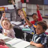 Smiling children raise their hands in a classroom