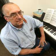 Brian Cade sits at the piano his wife purchased for him