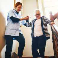 Caregiver helping senior woman down the stairs