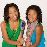 Sisters Chloe and Halle Bailey pose with a microphone