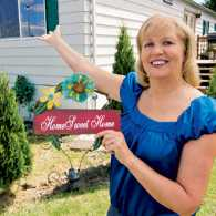 Barbara McCourtney stands proudly outside her home