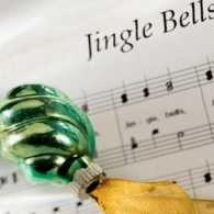 Jingle Bells sheet music and a green Christmas ornament with gold ribbon