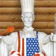 A statue of Abe Lincoln in chef's hat with kitchen tools in his hands