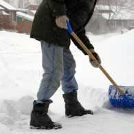 A young man shoveling deep snow