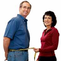 Mary wraps a tape measure around Tom's newly slim waist.