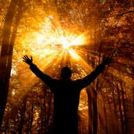 Man facing the sunlight with open arms