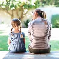 A mother sits on a porch as she converses with her young daughter