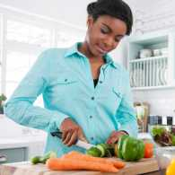 A woman in her kitchen chopping healthy vegetables to eat.