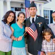 A young veteran poses with his family outside their home