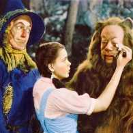 A Wizard of Oz lobby card featuring the Tin Man, the Scarecrow, Dorothy and the Cowardly Lioni