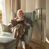 A senior reading a novel in his cozy home.