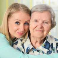 An adult daughter embraces her senior mother