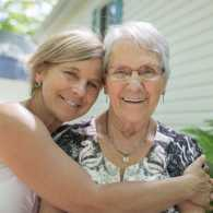A woman in her golden years embracing her aging mother.