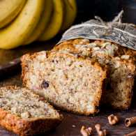 Sliced banana bread loaf with walnuts and cinnamon on wooden board.