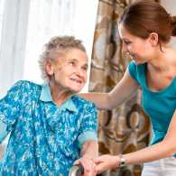 A young caregiver looks after an elderly loved one.