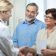 A middle-aged brother and sister discuss the parents' medical care with a doctor.