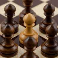 A light chess piece surrounded on all sides by dark ones