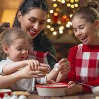 A mother does some Christmas baking with her two young daughters