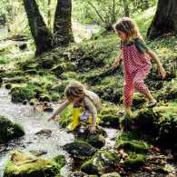Two young girls playing by a creek.