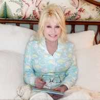 Dolly Parton sits on a bed in PJs, children's book in hand