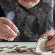 An elderly woman counting her change from her coin purse.
