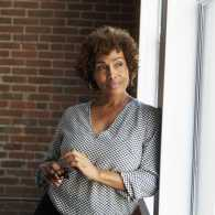 smiling woman stands by the window against a brick wall