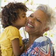 A grandmother receives a kiss from her granddaughter.
