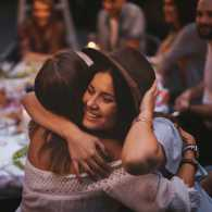 A happy woman gets hugs from her friends at a dimly lit restaurant