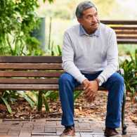 A man sitting on a park bench alone.