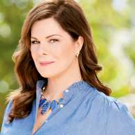 A portrait of Marcia Gay Harden in front of green scenery.