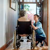 An aging woman in a wheelchair recieving in home care.