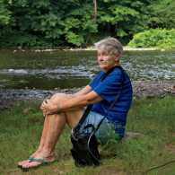 Judy sits on the banks of the Farmington River