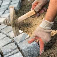 Gloved hands laying bricks in a patio